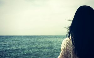 photo of a girl looking out at the ocean